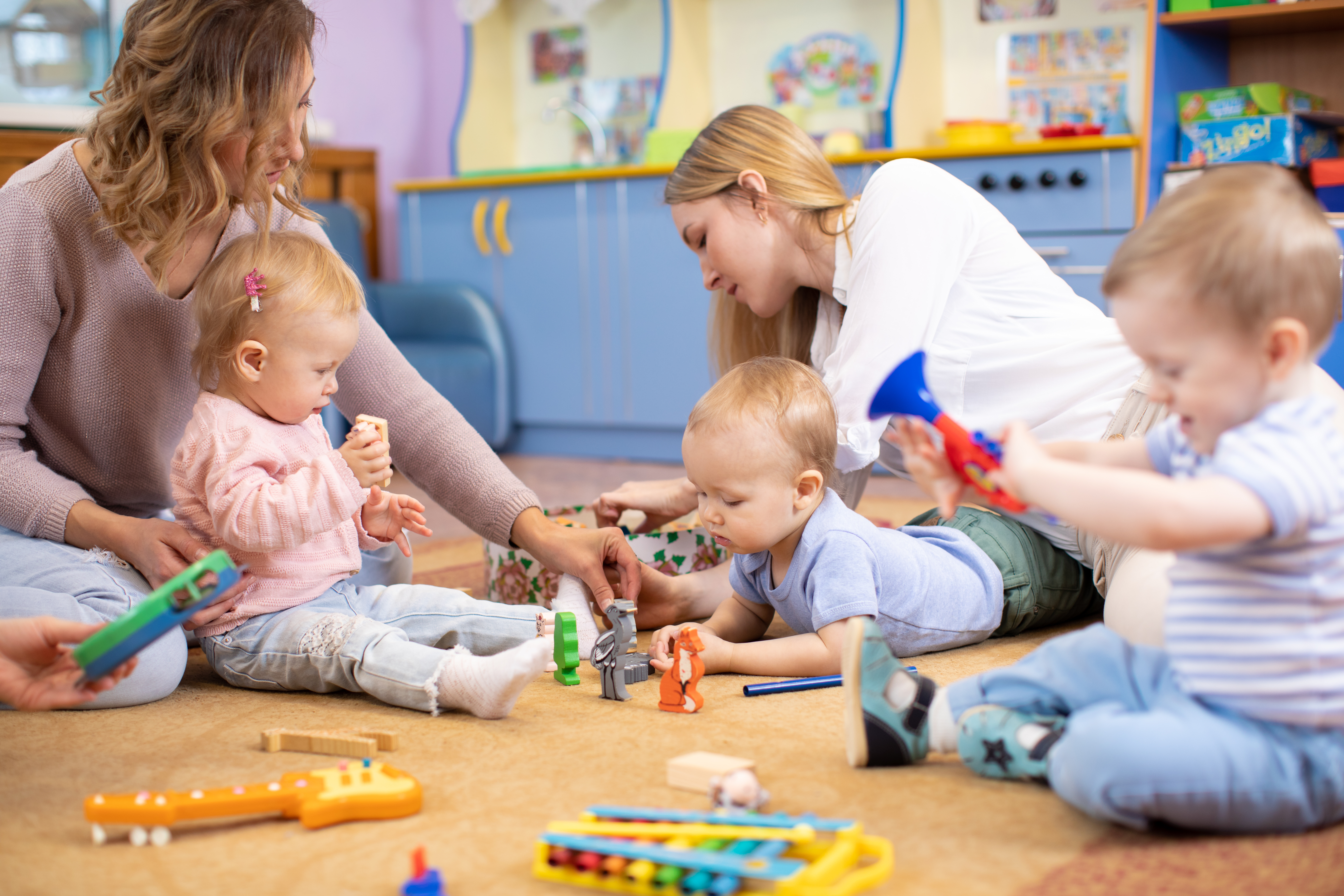 Toddlers playing with their care givers in a nursery at a school